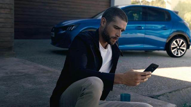 NOUVELLE PEUGEOT e-208 - Homme avec smartphone, Application MyPeugeot